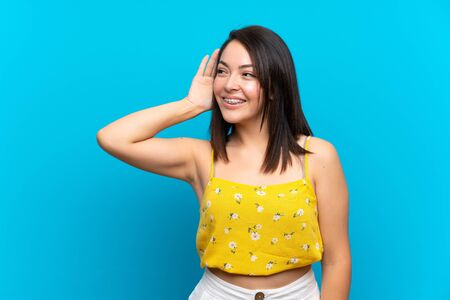 Young Mexican woman over isolated blue background listening something