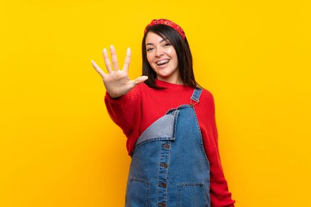 Young Mexican woman with overalls over yellow wall counting five with fingers