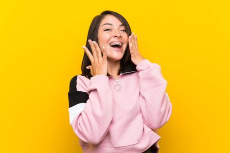 Young Mexican woman over isolated yellow background with surprise facial expression