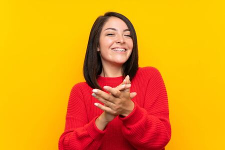 Young Mexican woman with red sweater over yellow wall applauding 写真素材