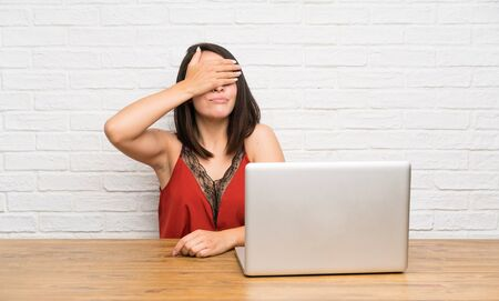 Young Mexican woman with a laptop covering eyes by hands Imagens
