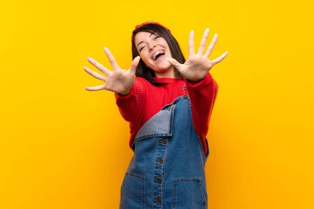 Young Mexican woman with overalls over yellow wall counting ten with fingers