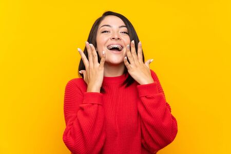 Young Mexican woman with red sweater over yellow wall with surprise facial expression