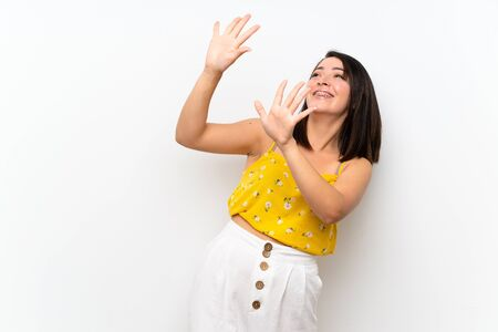 Young Mexican woman over isolated wall nervous and scared