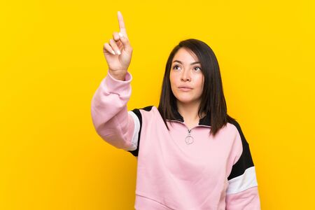 Young Mexican woman over isolated yellow background touching on transparent screen Stock fotó