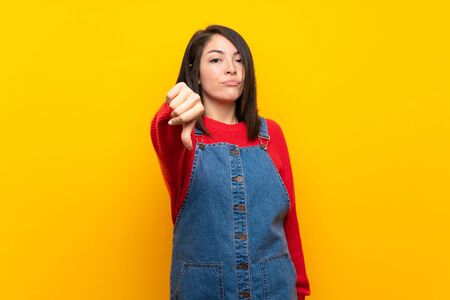 Young Mexican woman with overalls over yellow wall showing thumb down with negative expression