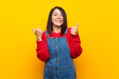 Young Mexican woman with overalls over yellow wall with thumbs up gesture and smiling Zdjęcie Seryjne
