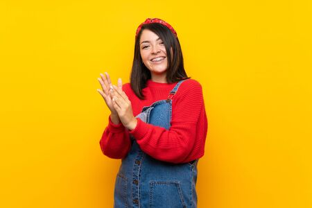 Young Mexican woman with overalls over yellow wall applauding after presentation in a conference