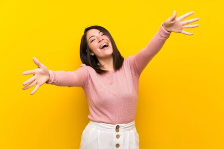 Young Mexican woman over isolated yellow background presenting and inviting to come with hand