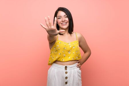 Young Mexican woman over isolated wall counting five with fingers