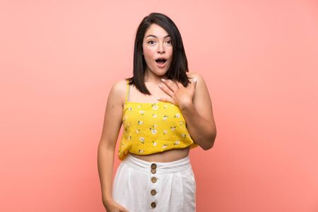 Young Mexican woman over isolated wall surprised and shocked while looking right