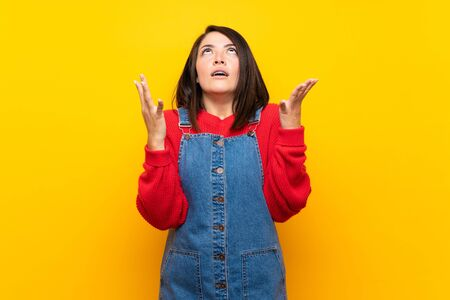 Young Mexican woman with overalls over yellow wall frustrated by a bad situation