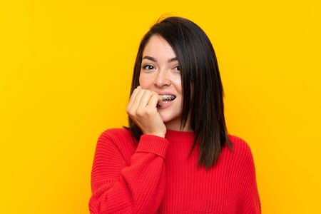 Young Mexican woman with red sweater over yellow wall nervous and scared