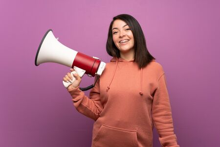 Young Mexican woman over isolated background holding a megaphone Imagens
