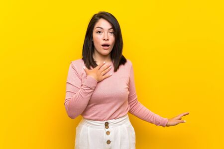 Young Mexican woman over isolated yellow background surprised and shocked while looking right