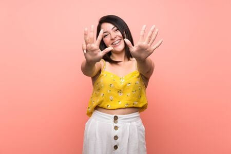 Young Mexican woman over isolated wall counting nine with fingers