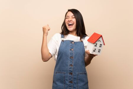 Young Mexican woman over isolated background holding a little house