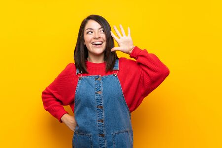 Young Mexican woman with overalls over yellow wall listening to something by putting hand on the ear