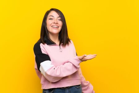 Giovane donna messicana su sfondo giallo isolato che allunga le mani di lato per invitare a venire