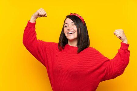 Junge mexikanische Frau mit rotem Pullover über gelber Wand, die einen Sieg feiert