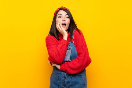 Young Mexican woman with overalls over yellow wall surprised and shocked while looking right