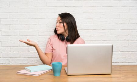 Young Mexican woman with a laptop holding copyspace imaginary on the palm Stock fotó
