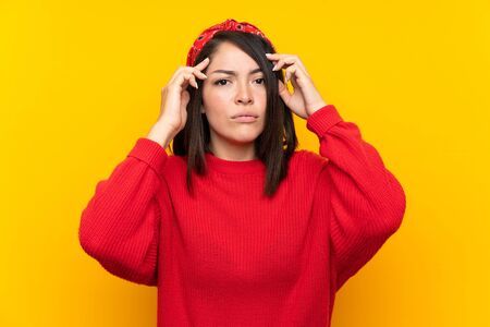 Young Mexican woman with red sweater over yellow wall unhappy and frustrated with something. Negative facial expression