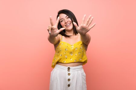 Young Mexican woman over isolated wall counting eight with fingers Zdjęcie Seryjne
