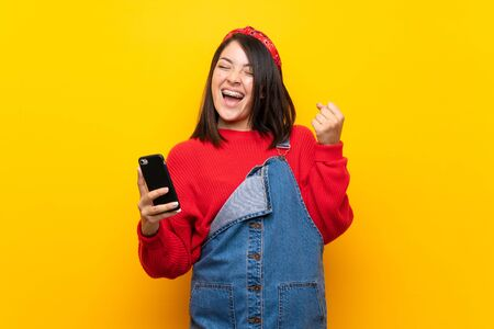 Young Mexican woman with overalls over yellow wall with phone in victory position