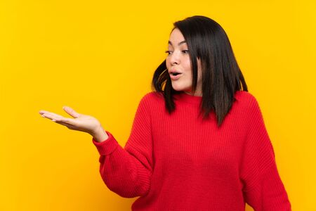 Young Mexican woman with red sweater over yellow wall holding copyspace imaginary on the palm