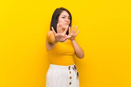 Young Mexican woman over isolated yellow background nervous stretching hands to the front Stock fotó - 130157620