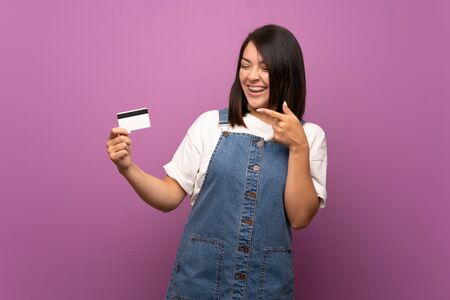 Young Mexican woman over isolated background holding a credit card Stock Photo