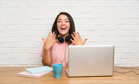 Young Mexican woman with a laptop with surprise facial expression