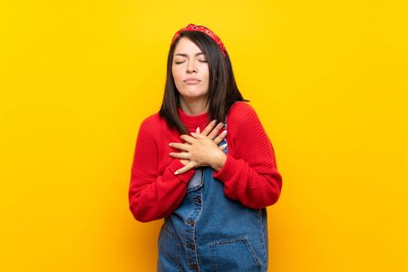 Young Mexican woman with overalls over yellow wall having a pain in the heart