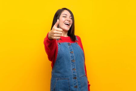 Young Mexican woman with overalls over yellow wall with thumbs up because something good has happened