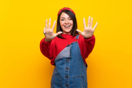 Young Mexican woman with overalls over yellow wall counting nine with fingers