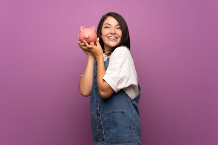 Young Mexican woman over isolated background holding a big piggybank
