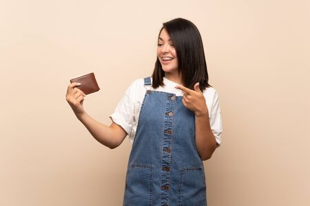 Young Mexican woman over isolated background holding a wallet