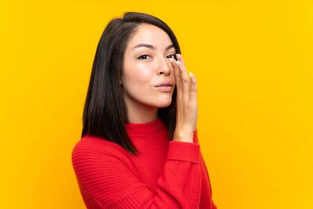 Young Mexican woman with red sweater over yellow wall whispering something Foto de archivo