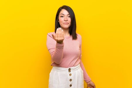 Young Mexican woman over isolated yellow background inviting to come with hand. Happy that you came Foto de archivo - 130157933