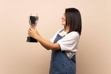 Young Mexican woman over isolated background holding a trophy Foto de archivo - 130157935