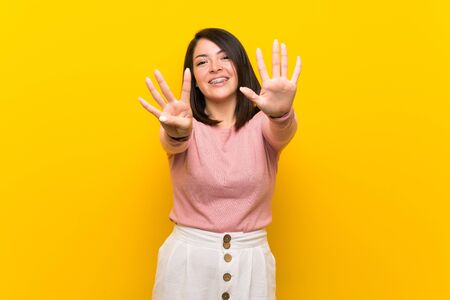 Young Mexican woman over isolated yellow background counting nine with fingers