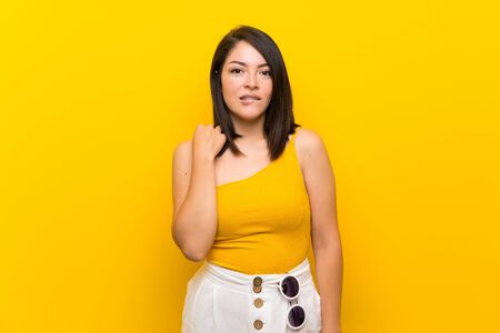Young Mexican woman over isolated yellow background with confuse face expression Foto de archivo - 130157948