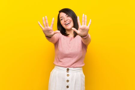 Young Mexican woman over isolated yellow background counting ten with fingers Foto de archivo - 130157962