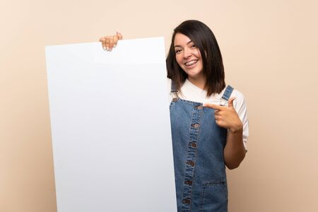 Young Mexican woman over isolated background holding an empty white placard for insert a concept Foto de archivo - 130157963