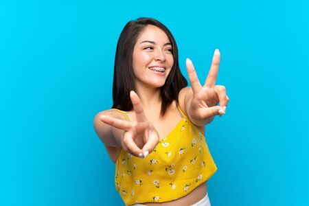 Young Mexican woman over isolated blue background smiling and showing victory sign