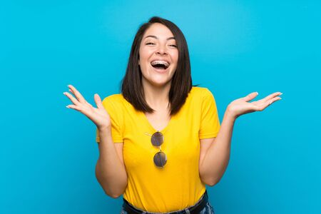 Young Mexican woman over isolated blue background with shocked facial expression