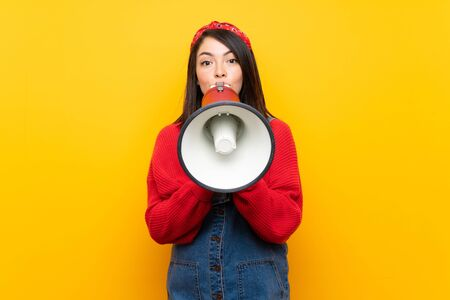 Young Mexican woman with overalls over yellow wall shouting through a megaphone Foto de archivo - 130157978