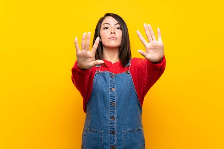 Young Mexican woman with overalls over yellow wall making stop gesture and disappointed Foto de archivo - 130157990