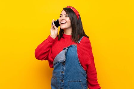 Young Mexican woman with overalls over yellow wall keeping a conversation with the mobile phone Foto de archivo - 130157993